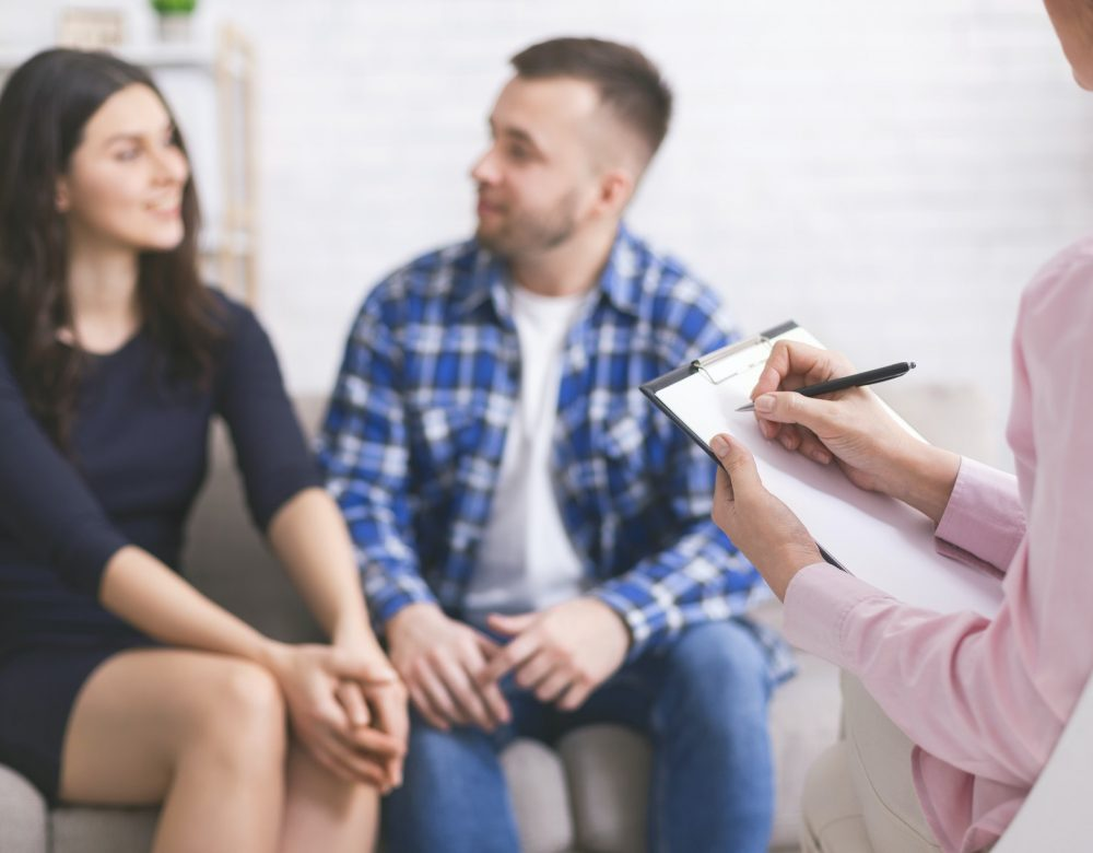 Young cheerful couple at consultation with family psychologist
